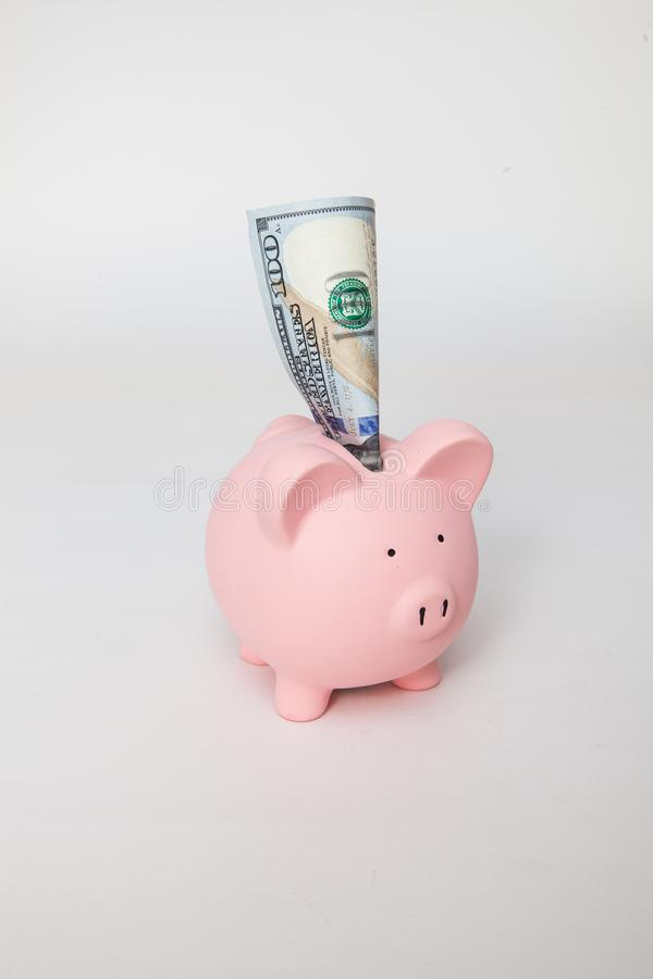 Piggy Bank with $100 sticking out stock photography