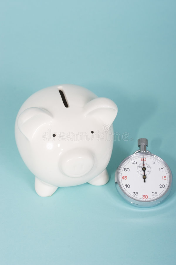 Piggy bank with a stop watch stock images