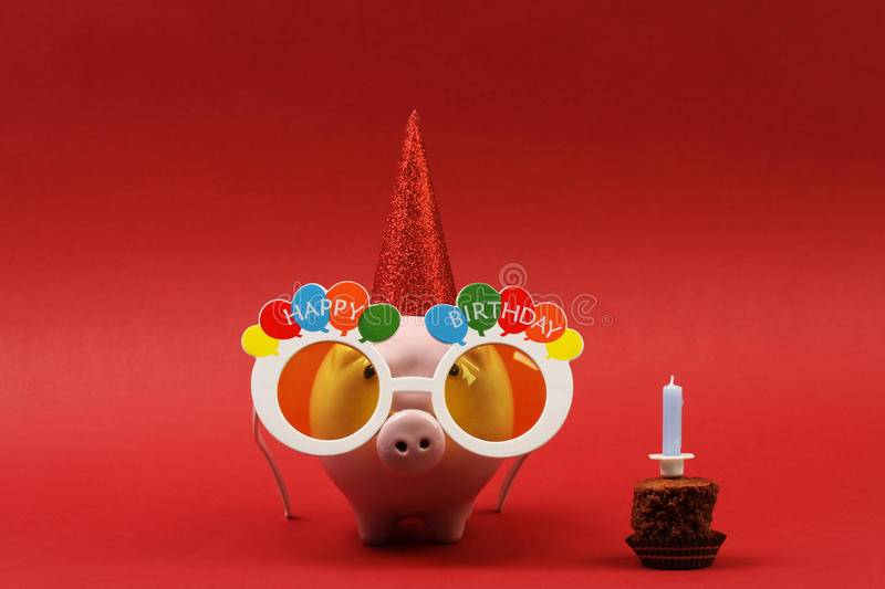 Piggy bank with sunglasses Happy birthday, party hat and birthday cake with candle on red background stock images