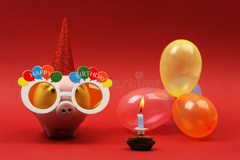 Piggy bank with sunglasses Happy birthday, party hat and multicolored party balloons on red background stock photos