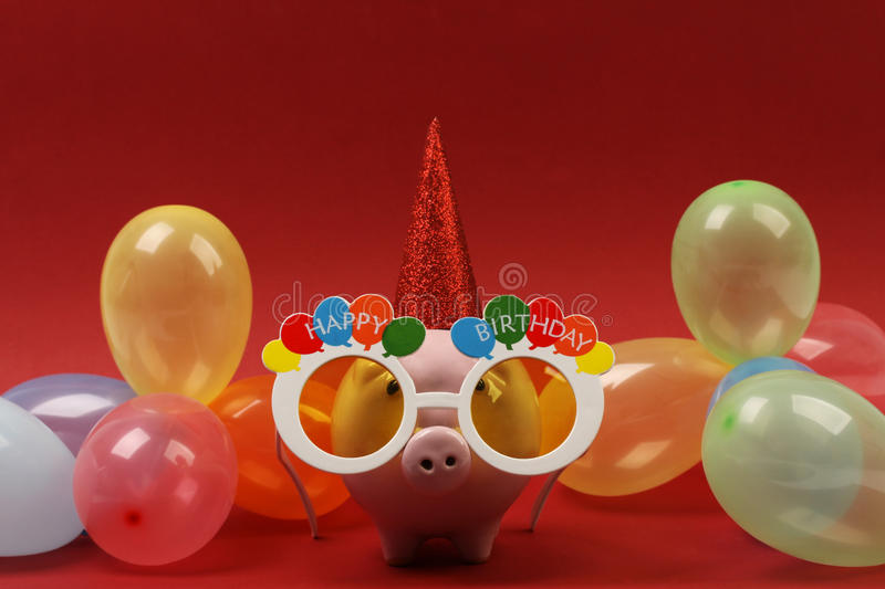 Piggy bank with sunglasses Happy birthday, party hat and multicolored party balloons on red background royalty free stock images