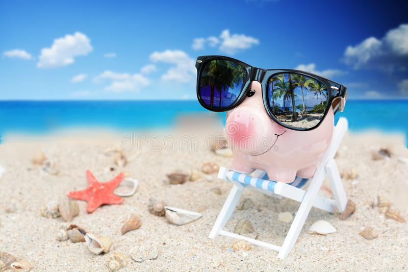 Piggy bank with sunglasses over deck chair, savings for holiday concept. Piggy bank with sunglasses over deck chair in the sand, savings for holiday concept stock photo