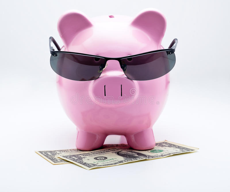 Piggy bank with sunglasses on U.S. dollars. Illustrating concepts of money royalty free stock photo