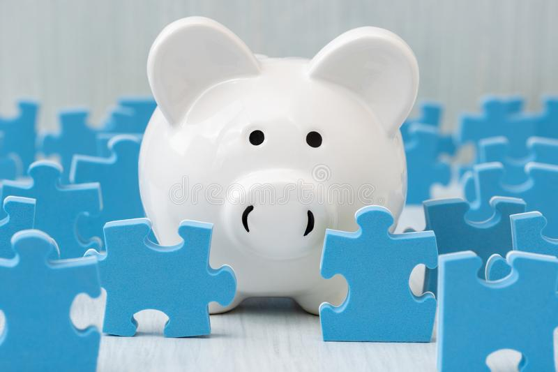 Piggy bank surrounded by puzzle pieces. Understanding the ins and outs of investing stock photo