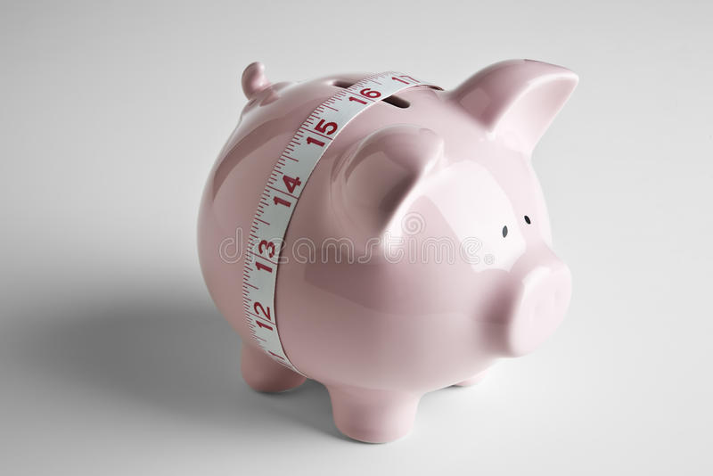 Piggy bank and tape measure royalty free stock photo