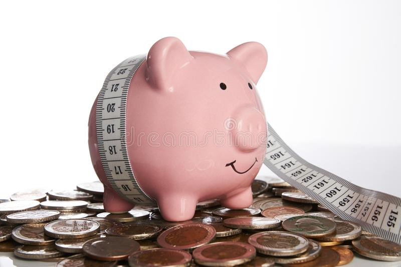 Piggy bank and tape measure standing on coins stock photos