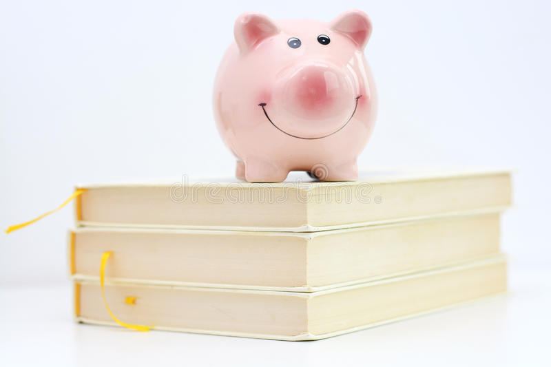 Piggy bank on top of pile of books suggesting saving for college concept royalty free stock photos