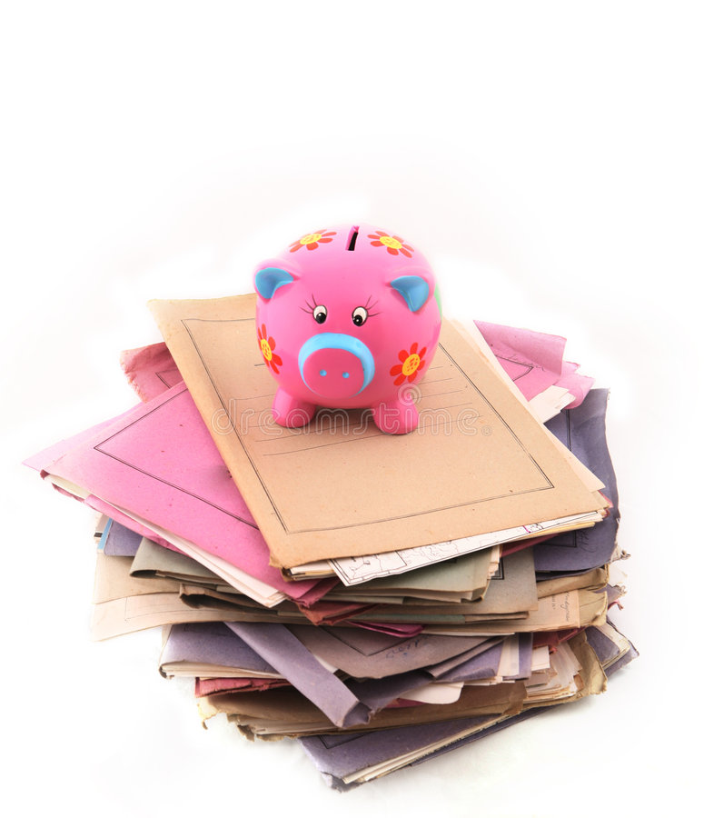 Piggy bank on top of stack of folders. Isolated stack of folders with piggy bank on top shot over white background royalty free stock image