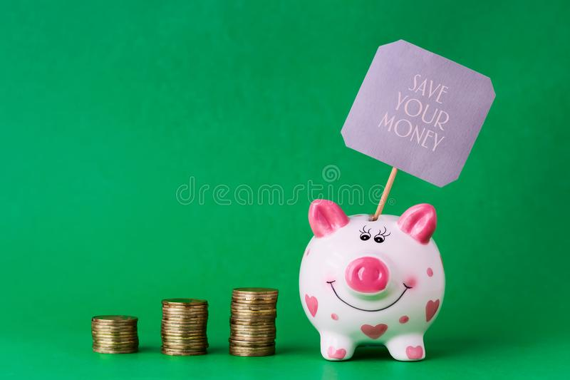 Piggy bank and towers coins. The inscription Save your money. Copy space. stock photos