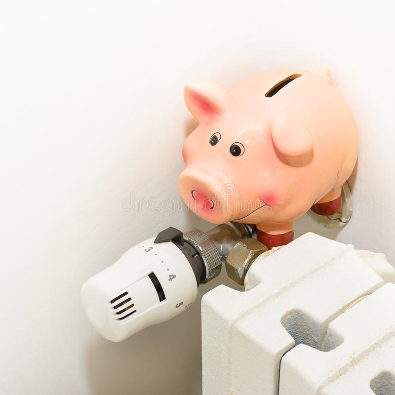 Piggy bank and the valve on the radiator for energy savings. The Piggy bank and the valve on the radiator for energy savings royalty free stock images
