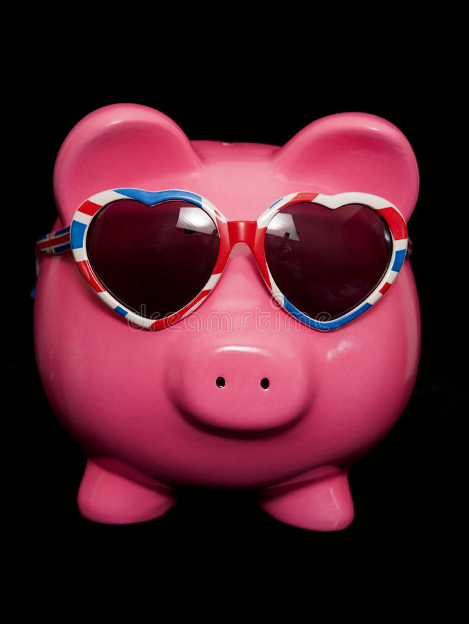 Piggy bank wearing union jack heart sunglasses. Cutout royalty free stock photos