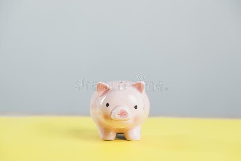 Piggy bank  on yellow table stock images
