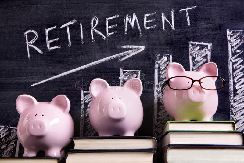 Piggybank retirement planning savings growth chart. Three pink piggy banks standing on books next to a blackboard with retirement savings chart. Sharp focus on stock images