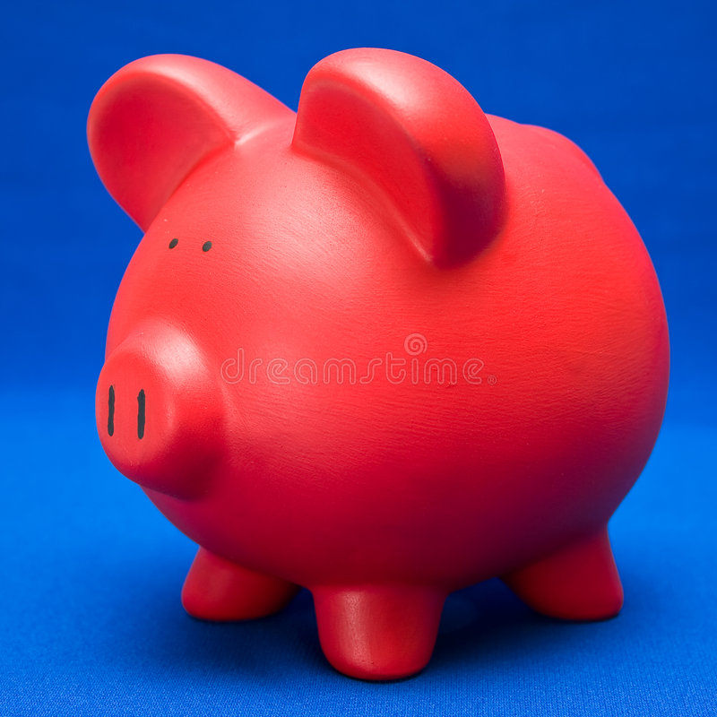 Piggy on Blue. Red piggy bank on blue fabric background stock photography