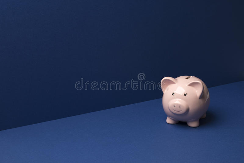 Piggy Coin Bank Over Blue Background Copy Space. Piggy coin bank on a blue wall and floor background with copy space stock photos