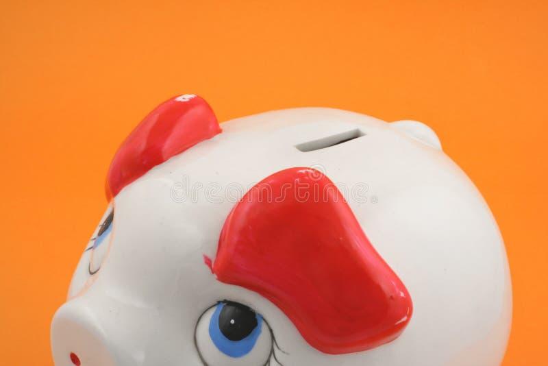 Piggy Querneigung auf Orange lizenzfreie stockfotografie