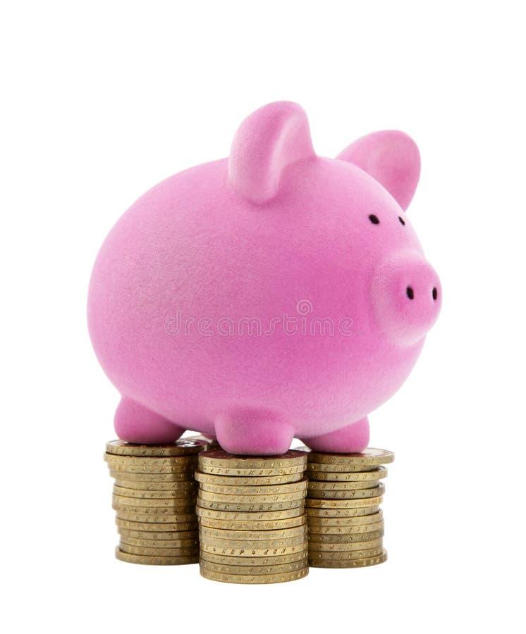 Piggy Querneigung auf Stapeln Münzen stockfotos