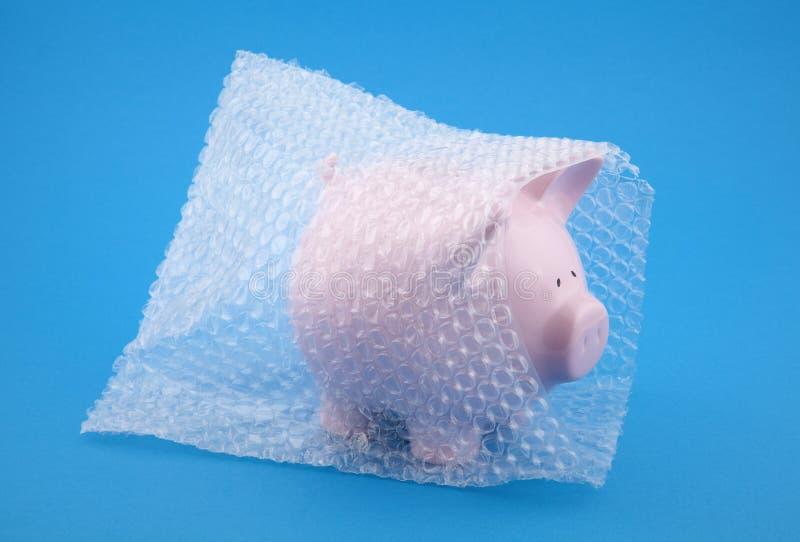 Piggy Querneigung in der Luftblasenverpackung auf blauem Hintergrund lizenzfreie stockfotos
