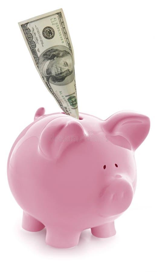 Piggy Querneigung mit $100 im Schlitz lizenzfreie stockbilder