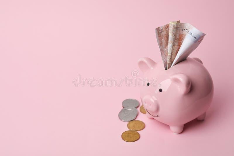 Piggy Querneigung mit Geld lizenzfreie stockbilder