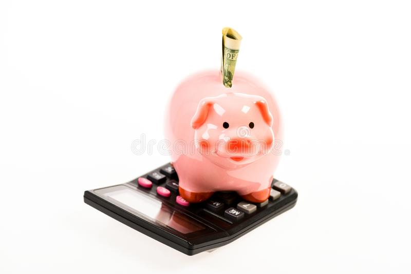 Piggy Querneigung mit Rechner moneybox Berechnung des Jahreseinkommens Stecken eines Geldes in eine piggy Querneigung Erstes Geha stockfotos