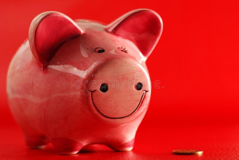 Piggy Querneigung und Münze lizenzfreie stockfotos