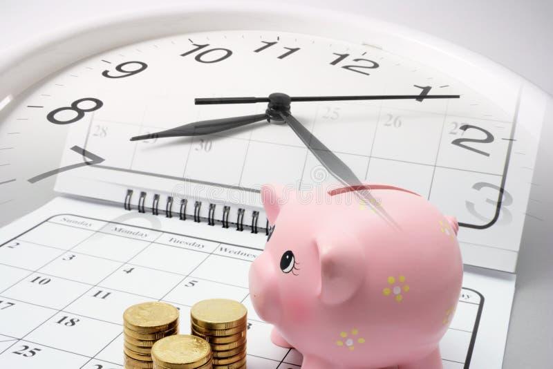 Piggy Querneigung und Münzen auf Kalender lizenzfreies stockfoto