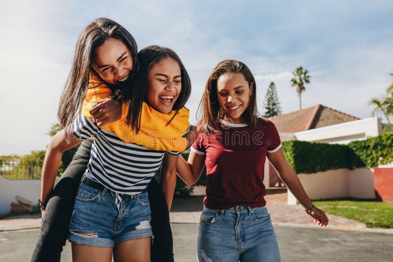 Piggy ridning för flicka på hennes vän arkivbild