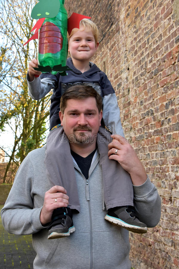 Piggyback with daddy. Toddler boy on the shoulders of his dad holding a handmade lantern for martin procession stock photos