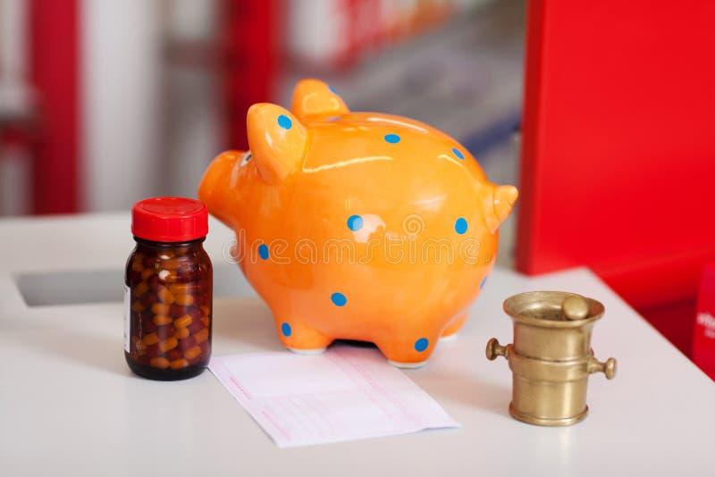 Piggybank, μπουκάλι χαπιών, Μπιλ, κονίαμα και γουδοχέρι στον πίνακα στοκ φωτογραφία