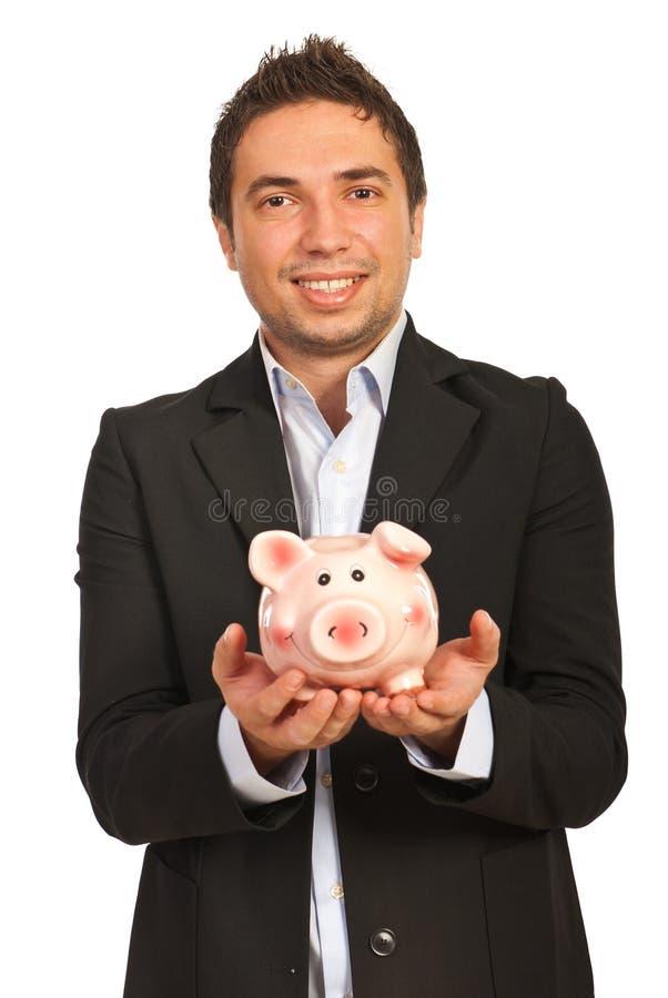 Piggybank удерживания бизнесмена стоковая фотография rf