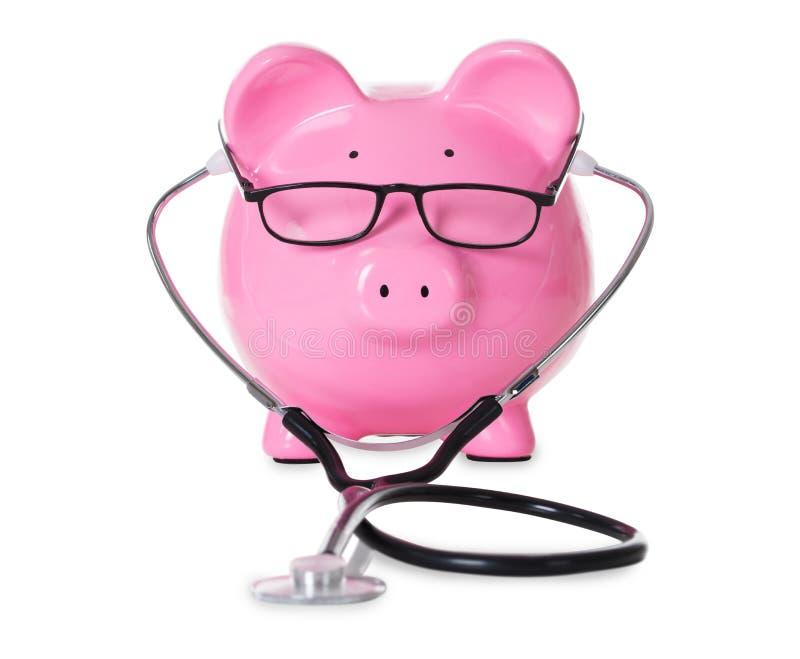 Piggybank con el estetoscopio y las lentes fotos de archivo libres de regalías