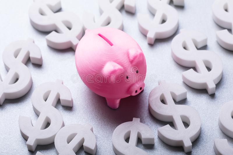 Piggybank cor-de-rosa cercado por muitos sinais de moeda do Euro fotos de stock