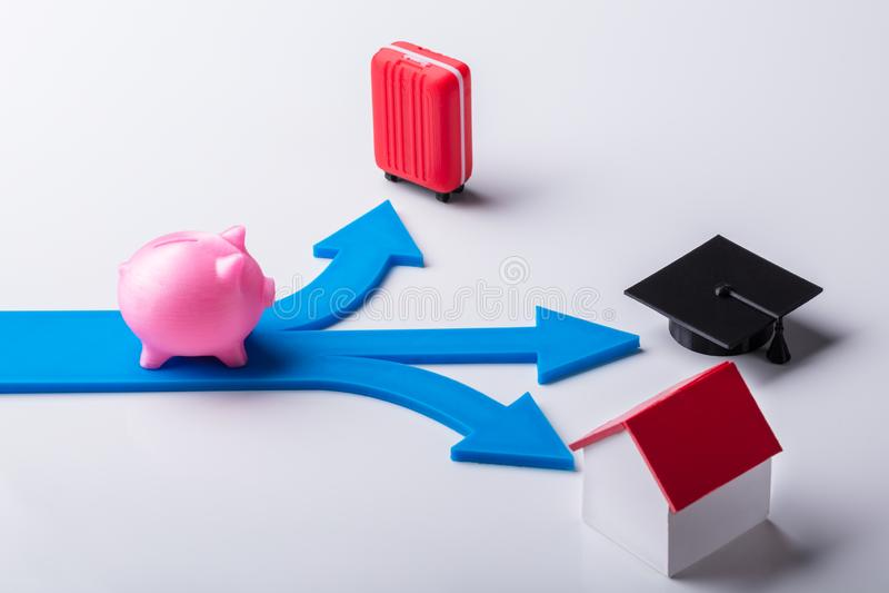 Piggybank cor-de-rosa nas setas azuis que mostram várias escolhas fotos de stock royalty free
