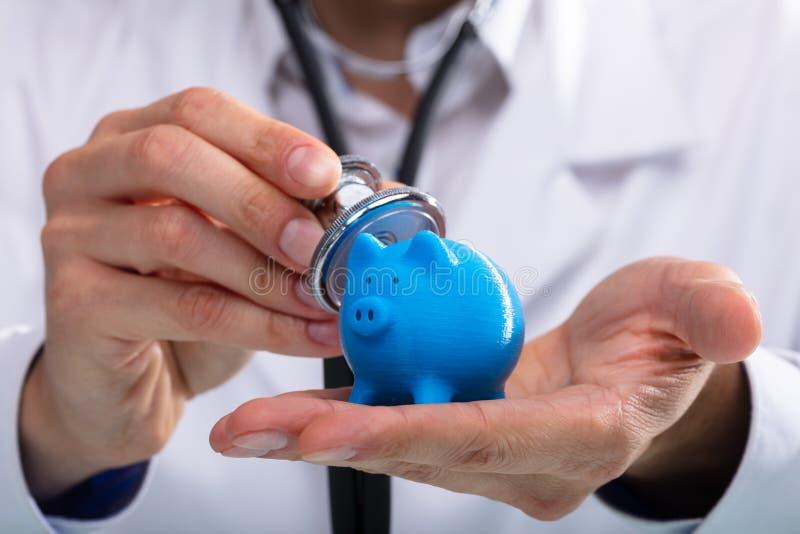 Piggybank de exame do doutor com estetosc?pio imagens de stock