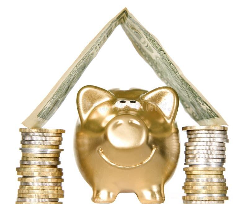 Piggybank de oro con el hogar del dinero imágenes de archivo libres de regalías