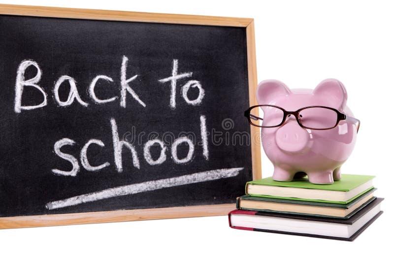 Piggybank de volta ao lembrete da mensagem da escola, conceito das taxas da escola, isolado fotografia de stock