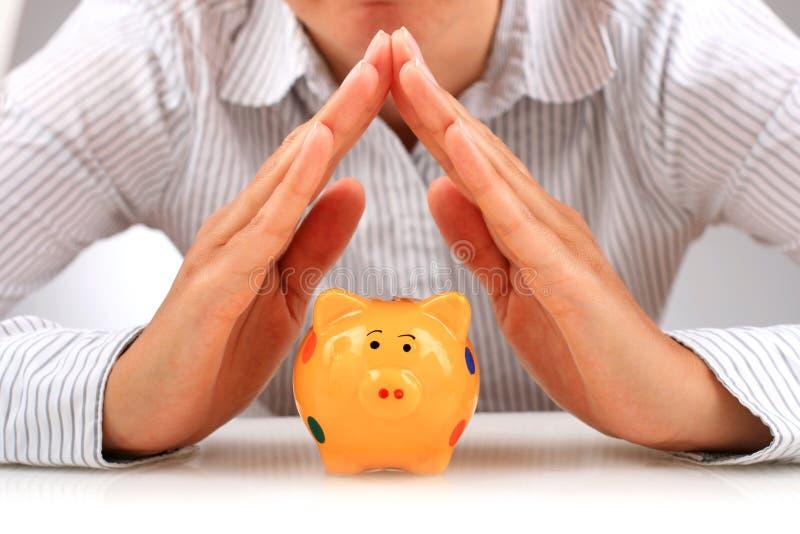 Piggybank e mãos. fotos de stock royalty free
