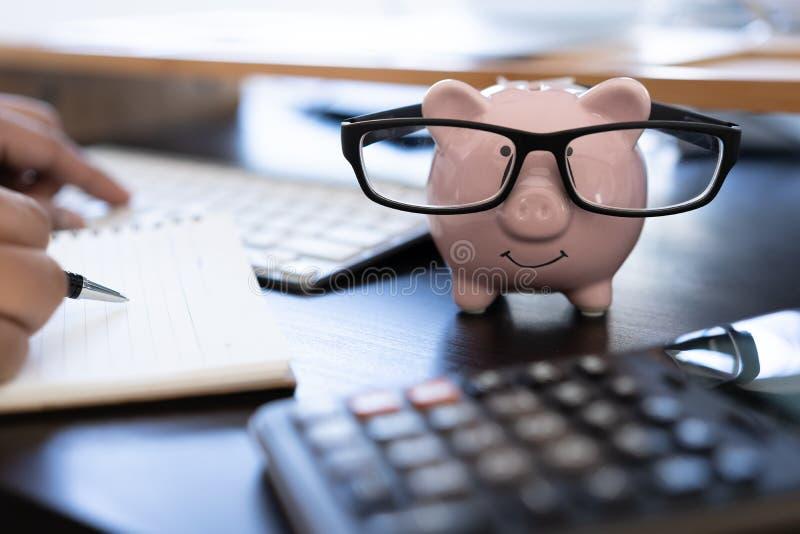 piggybank en Calculator op het tellende geld Bureau van de bedrijfsdocumentcalculator stock afbeeldingen