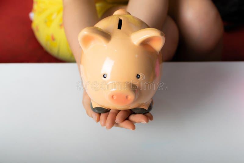 Piggybank för kvinnahandhåll royaltyfria bilder