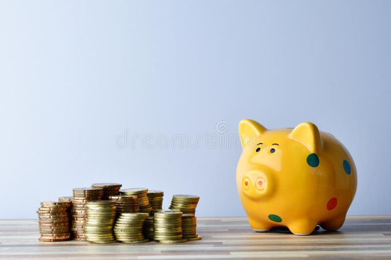 Piggybank and gold coins stock images