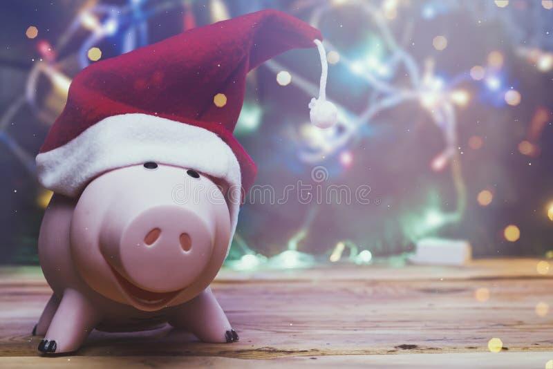 Piggybank med jultomtehatt mot dekorerat xmas-träd Juli Spara pengar till jul Förstklassig användning royaltyfria foton