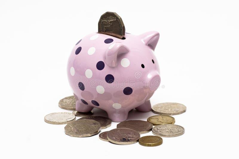Piggybank met een muntstuk daarin en rond het stock foto's