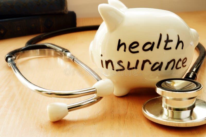 Piggybank mit Wörtern auf einer Seitenkrankenversicherung lizenzfreie stockbilder