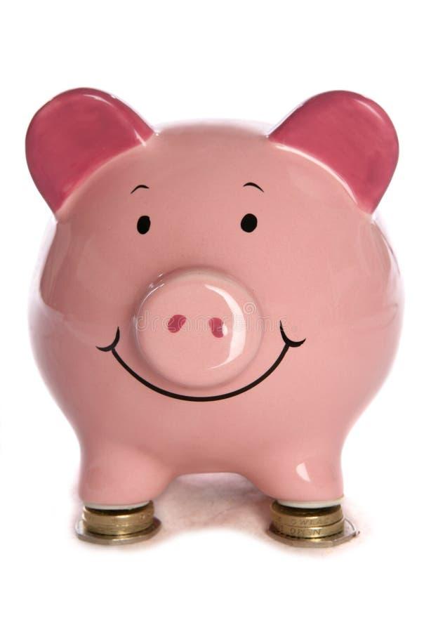 Piggybank que descansa em moedas de libra imagem de stock