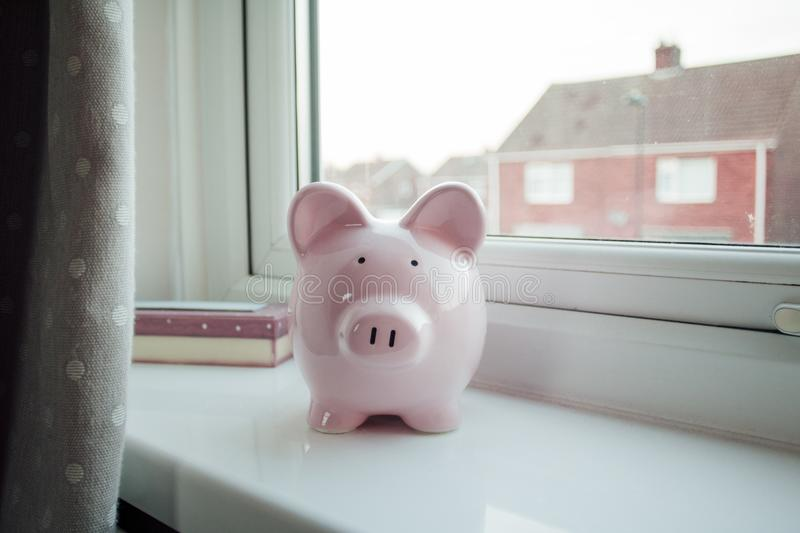 Piggybank on a Windowsill. Piggybank stands on a windowsill in a home royalty free stock image