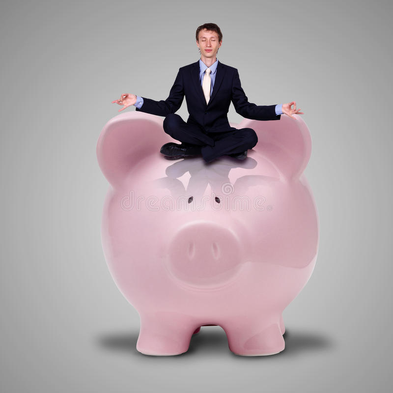 Piggybank and young business man royalty free stock photo
