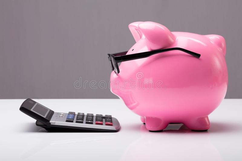 Piggybank z eyeglasses i kalkulatorem obraz stock