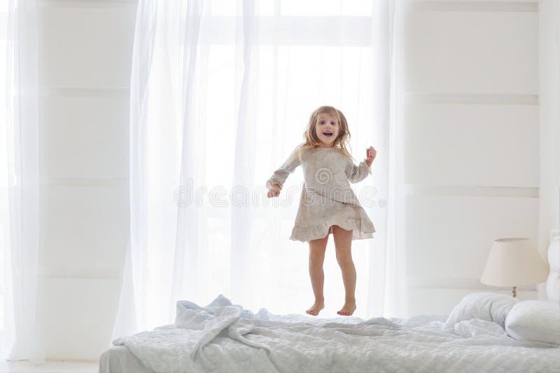 Pigiami bianchi d'uso della bambina felice che saltano sul letto in camera da letto bianca immagine stock