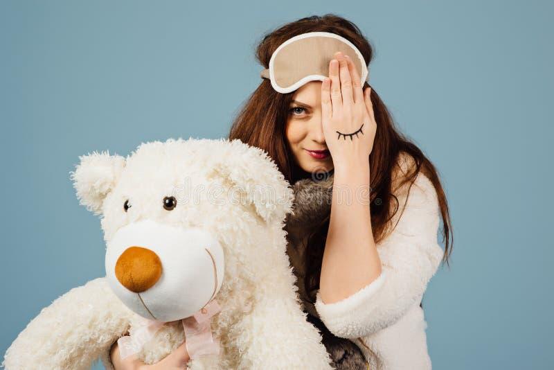 Pigiami d'uso di una bella giovane donna che abbracciano il suo orsacchiotto farcito fotografie stock libere da diritti